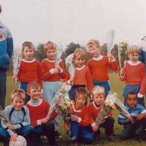 Jeugdfoto van Mo Hersi op het voetbalveld met zijn team en trainers