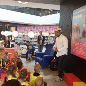 Sfeerbeeld van Mo Hersi die vertelt aan kinderen in de nieuwe Bibliotheek van Almere Centrumvertelt