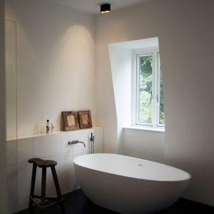 Sfeerfoto van moderne badkamer met houten details en rond bad