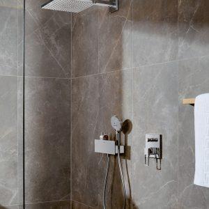 Sfeerbeeld van douchecabine met grijze natuurstene tegels en chrome afwerking