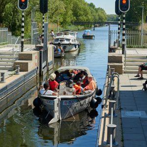 Foto van een boot met mensen die door een sluis vaart