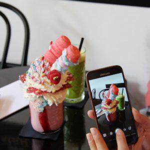 Close-up van iemand die met een telefoon een foto maakt van een milkshake