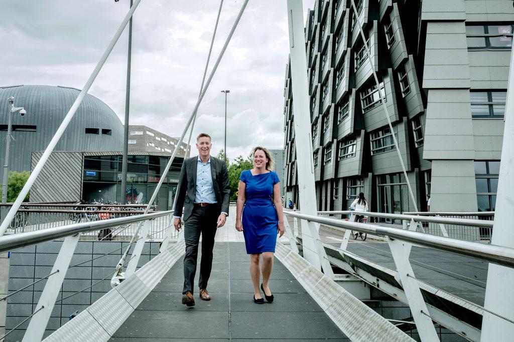 Foto van een man en vrouw die over een brug lopen