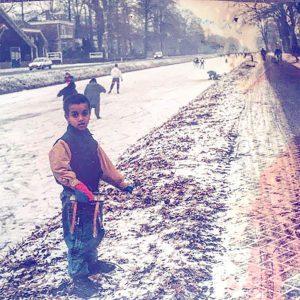 Jeugdfoto van Mo Hersi met schaatsen in zijn hand naast het bevroren en besneeuwde kanaal