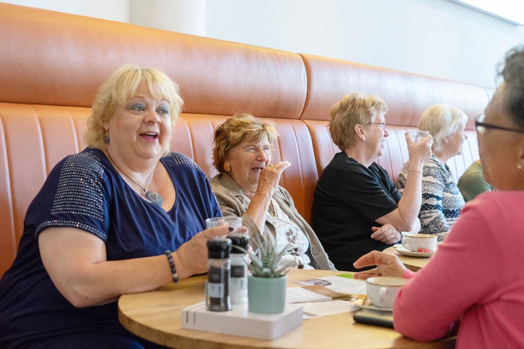 Sfeerbeeld van lachende dames aan tafel in een restaurant