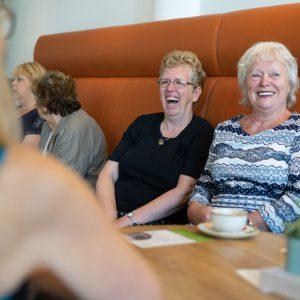 Sfeerbeeld van lachende dames op een bank in een restaurant