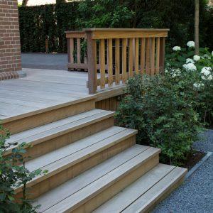 Detail foto van een houten veranda trap grenzend aan een antraciet grindpad