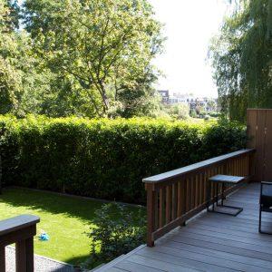 Sfeerfoto van een veranda met loungebank met uitkijk over een groene tuin