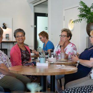 Sfeerbeeld van mensen die conversatie voeren aan een tafel in een restaurant