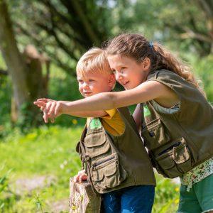 Foto van kinderen in de natuur die ergens naar wijzen