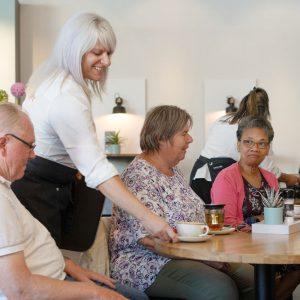 Sfeerbeeld van mensen aan tafel en een serveerster die koffie brengt