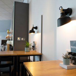 Close-up van een tafel met menukaart en plant in het restaurant Mockamore