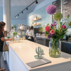Scherpte diepte foto van en een mevrouw die iets besteld aan de balie van een restaurant waar bloemen op staan