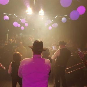 Sfeerbeeld van mensen in een zaal die muziek maken op blaasinstrumenten