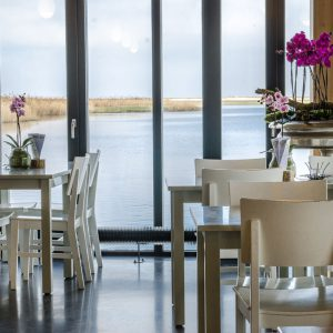 Sfeerfoto van tafels in een restaurant met uitzicht over het water