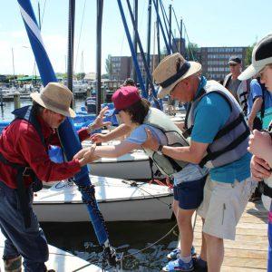 Sfeerbeeld van jongeren en begeleiding in een haven die op een zeilboot stappen