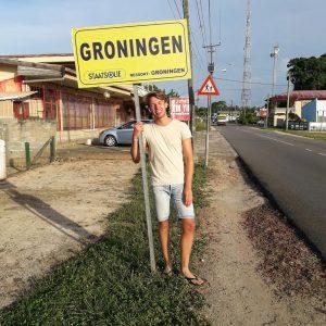 Foto van een jongeman die naast de weg staat met een geel bord in zijn hand waar Groningen op staat