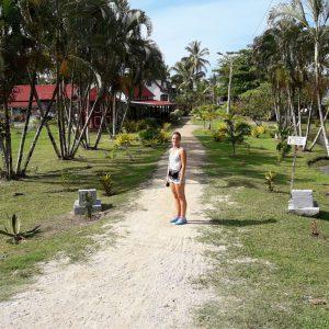 Buitenfoto van een zomers geklede vrouw op een pad tussen de palmbomen
